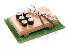 Le maki de sushi a placé avec les saumons et le concombre et la branche de Sakura Photo stock