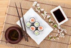 Le maki de sushi a placé avec les saumons et le concombre et le thé vert Images libres de droits