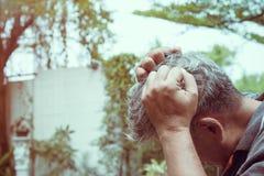 Le mal de tête de sensation de vieil homme tandis que déprimé photographie stock libre de droits