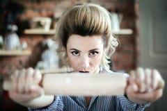 Le mal sexy de femme au foyer de fille regarde la caméra et tient une goupille devant la caméra dans le plan rapproché de cuisine photo stock