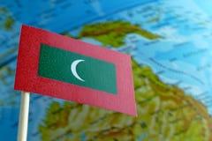Le Maldive diminuiscono con una mappa del globo come fondo Fotografia Stock