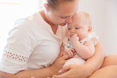 Le mamman behandla som ett barn omsorger för hennes lilla ledset flickan Arkivfoton