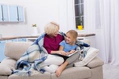 Le mamman och hennes sjuka dotter som hemma blir, läseböcker royaltyfri foto