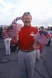 Le man med US-flaggor Arkivfoto