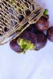 Le mangoustan dans le panier traditionnel sont capturés a isolé dans l'angle supérieur Photo stock