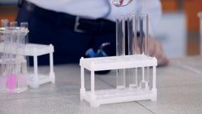 Le mani aggiungono i reagenti chimici nella fiala, provetta Studente che effettua la prova di chimica in laboratorio video d archivio