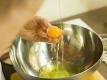 Le mani aggiungono l'uovo in una ciotola Fotografie Stock Libere da Diritti