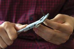 Le mani alte vicine dell'uomo tengono il calibro e misurano i pezzi f del metallo fotografia stock libera da diritti