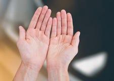 Le mani aprono insieme il raggiungimento contro il fondo vago Fotografia Stock Libera da Diritti