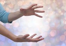 Le mani aprono irregolare con il fondo leggero scintillante del bokeh Immagini Stock Libere da Diritti