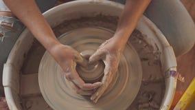 Le mani in argilla con attenzione e toccano delicatamente la ruota del ` s del vasaio di dipendere video d archivio