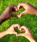 Le mani in bianco e nero nel cuore modellano, concetto interrazziale di amicizia immagini stock libere da diritti