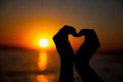 Le mani che formano un cuore modellano con la siluetta del tramonto Fotografia Stock Libera da Diritti
