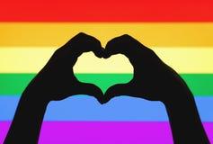Le mani che mostrano il cuore firmano sulla bandiera dell'arcobaleno di LGBT e di gay pride immagine stock libera da diritti