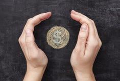 Le mani che proteggono il dollaro disegnato coniano sul backgroun nero della lavagna Fotografia Stock