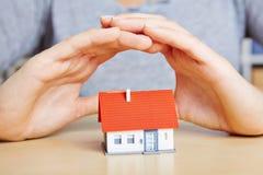 Le mani che proteggono la casa gradiscono l'assicurazione Fotografie Stock