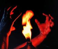 Le mani che provano a toccare il fuoco immagine stock libera da diritti
