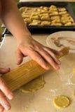 Le mani che rotolano una pasta modellano per il biscotto Immagini Stock
