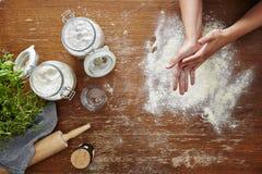 Le mani che spolverano la scena di cottura della farina flour sulla tavola di legno Fotografia Stock Libera da Diritti