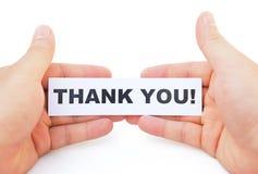 Le mani che tengono la carta di vi ringraziano Immagine Stock