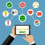 Le mani che tengono un computer della compressa con la valutazione stars La valutazione stars il app con cinque stelle dorate Fotografia Stock Libera da Diritti