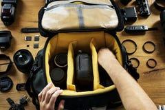 Le mani che tengono una preparazione della borsa della macchina fotografica hanno messo un'attrezzatura dentro fotografia stock