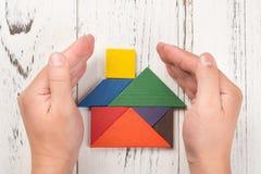 Le mani circondano una casa di legno fatta dal concetto di assicurazione della casa del tangram Fotografie Stock