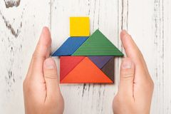 Le mani circondano una casa di legno fatta dal concetto di assicurazione della casa del tangram e che rappresenta la proprietà do immagine stock