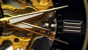 Le mani commoventi dell'orologio contro lo sfondo del meccanismo nudo dell'orologio stock footage