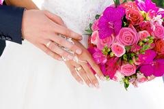 Le mani con le fedi nuziali sui precedenti della damigella d'onore bianca si veste fotografia stock