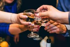 Le mani con i bicchieri di vino e gli amici della vodka celebrano Fotografia Stock Libera da Diritti