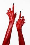 Le mani con i chiodi neri, mani rosse di Satana, tema del diavolo rosso di Halloween, su un fondo bianco, isolato immagine stock