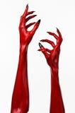 Le mani con i chiodi neri, mani rosse di Satana, tema del diavolo rosso di Halloween, su un fondo bianco, isolato fotografia stock libera da diritti
