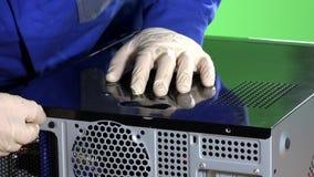 Le mani con i guanti collegano i cavi e chiudono la copertura riparata della cassa del computer video d archivio