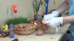 Le mani con i guanti hanno messo le coperture della cipolla e l'uovo bianco nel calzino stock footage