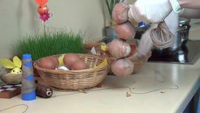 Le mani con i guanti hanno messo le coperture della cipolla e l'uovo bianco nel calzino e nella corda video d archivio