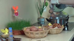 Le mani con i guanti hanno messo il calzino arrivato a fiumi uova nell'acqua d'ebollizione del vaso con pittura video d archivio