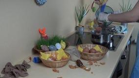 Le mani con i guanti hanno messo le uova avvolte in calzino nell'acqua d'ebollizione del vaso con pittura stock footage