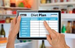 Le mani con la compressa facendo uso della dieta progettano il App davanti al frigorifero o al frigorifero aperto Fotografie Stock Libere da Diritti