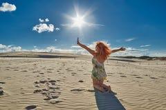 Le mani d'ondeggiamento della donna Redheaded felice fra le dune di Leba abbandonano Immagine Stock