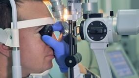 Le mani degli oftalmologi in guanti tengono una lente ad un occhio dei pazienti