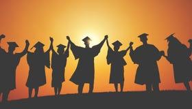 Le mani degli studenti del gruppo hanno sollevato il concetto della siluetta di graduazione Fotografia Stock Libera da Diritti