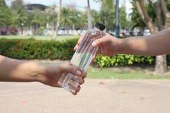 Le mani degli uomini è di dare una bottiglia immagini stock
