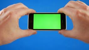 Le mani degli uomini che tengono lo smartphone in una posizione orizzontale Schermo verde sul telefono e sul chromakey blu Nessun video d archivio