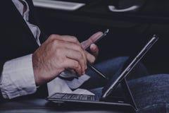 Le mani degli uomini d'affari stanno funzionando con i computer portatili sulle automobili mentre viaggiando fotografie stock