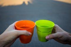 Le mani degli uomini e della donna che giudicano tazza calda di tè all'aperto al tramonto Fotografie Stock