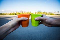 Le mani degli uomini e della donna che giudicano tazza calda di tè all'aperto al tramonto Fotografia Stock Libera da Diritti
