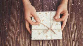 Le mani degli uomini hanno annodato il contenitore di regalo della corda, il regalo per il Natale ed il nuovo anno, fondo di nata immagini stock libere da diritti