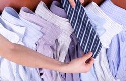 Le mani degli uomini tengono il legame sopra le camice Fotografia Stock Libera da Diritti