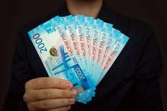 Le mani degli uomini tengono un pacchetto di nuove fatture da 2.000 rubli Immagini Stock Libere da Diritti